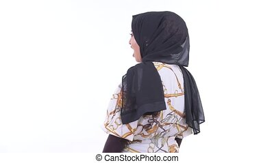 Rear view of young African Muslim woman thinking and looking around