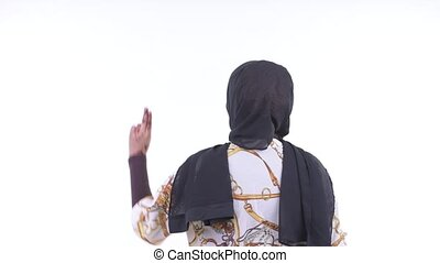 Rear view of young African Muslim woman touching something