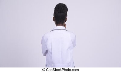 Rear view of young African woman doctor thinking - Studio...