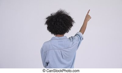 Rear view of young African woman pointing finger - Studio...