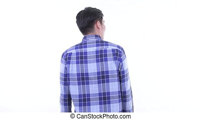 Rear view of young Asian hipster man thinking and looking around