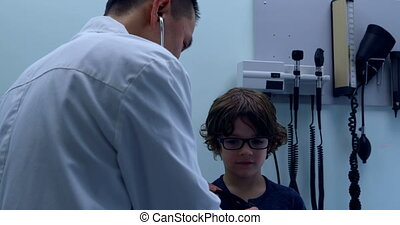 Rear view of young asian male doctor examining caucasian boy patient chest in a clinic 4k