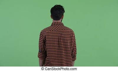 Rear view of young bearded Persian hipster man thinking and looking around