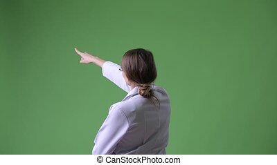 Rear view of young beautiful woman doctor pointing finger...