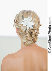 Rear view of young blonde bride with a chick coiffure