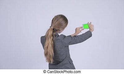 Rear view of young blonde businesswoman taking picture with...