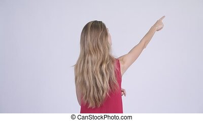 Rear view of young blonde woman directing and pointing...