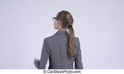 Rear view of young businesswoman directing and pointing...