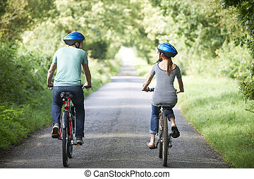 Rear View Of Young Couple Cycling On Country Lane
