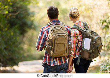 rear view of young couple hiking in mountain