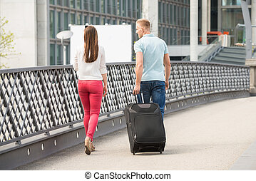 Couple Walking On Bridge With Luggage