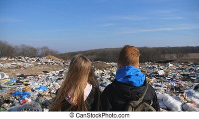 Rear view of young girl and boy stands against the blurred background of dirty garbage dump. Little children looks at trash on junkyard. Concept of environmental pollution problem. Close up.
