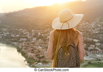Rear view of young girl in hat on city background. Woman watching the sunset