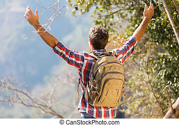 hiker with arms open on top of the mountain