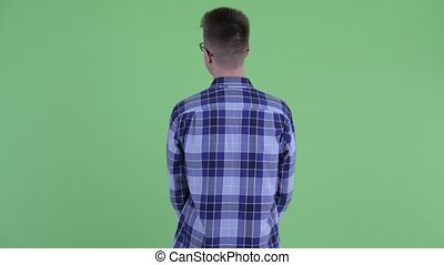 Rear view of young hipster man thinking and looking around