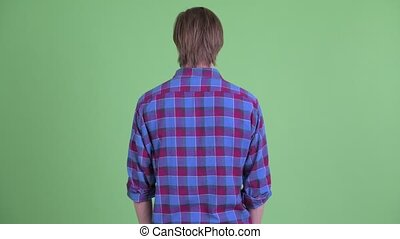 Rear view of young hipster man thinking while looking around
