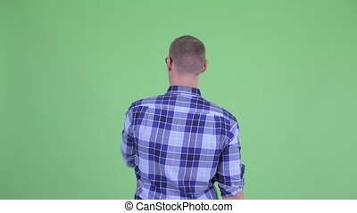 Rear view of young hipster man touching something