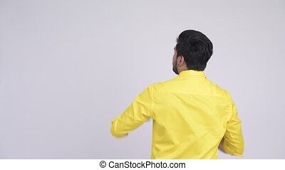 Rear view of young Indian businessman directing and pointing...
