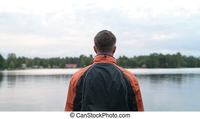 Rear View Of Young Man Enjoying The View Of The Lake -...