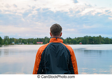 Rear View Of Young Man Enjoying The View Of The Lake