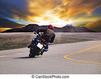 rear view of young man riding motorcycle in asphalt road...