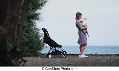 Rear view of young mother sitting at the beach with baby stroller