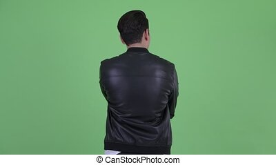 Rear view of young multi ethnic man thinking and looking around