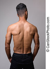 Rear view of young muscular Persian man shirtless