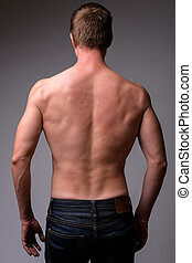 Rear view of young muscular shirtless man
