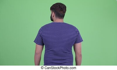 Rear view of young overweight bearded Indian man thinking and looking around