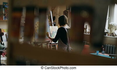 Rear view of Young painter girl in apron painting still life picture on canvas in art-class