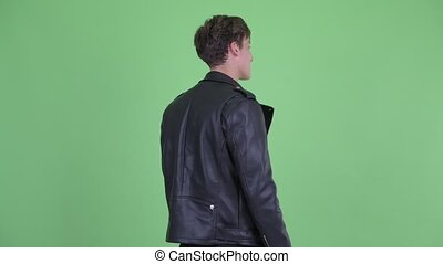Rear view of young rebellious man thinking and looking around
