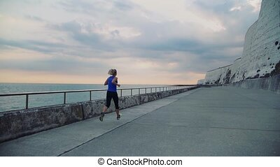 Rear view of young sporty woman runner running by the sea in...