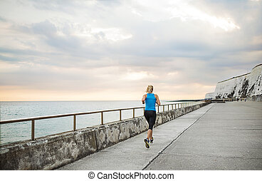 Rear view of young sporty woman runner running on the beach outside.