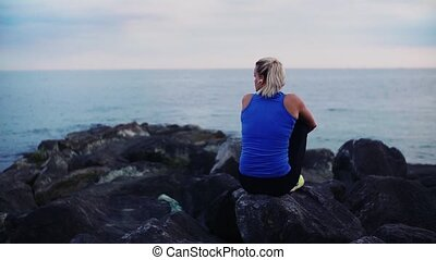 Rear view of young sporty woman runner sitting on rocks on...
