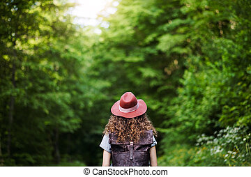 Rear view of young tourist woman traveller with backpack walking in nature.