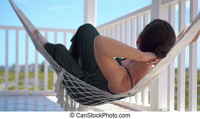 Rear view of young woman enjoying a sunny day in the hammock on her terrace
