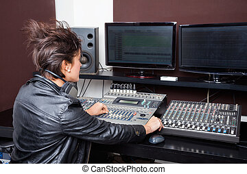 Rear View Of Young Woman Mixing Audio