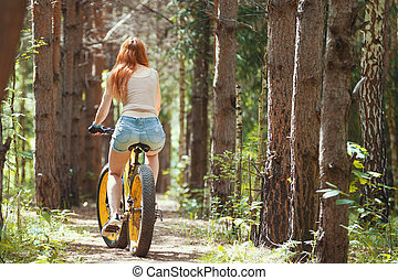 Rear view of young woman on fat bike in the woods