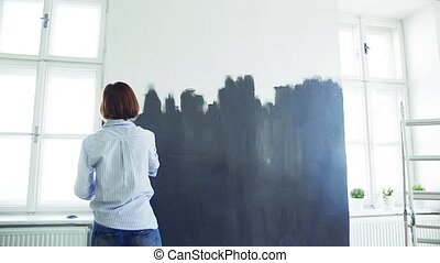 Rear view of young woman painting wall black. A startup of...