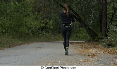 young woman running on road in autumn woods - rear view of...