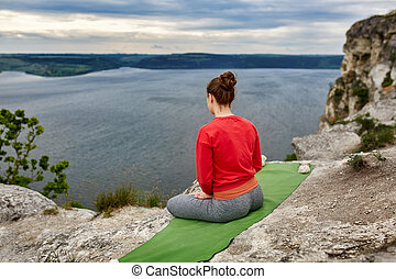 Rear view of young woman sitting in lotus position on the rock over the river.
