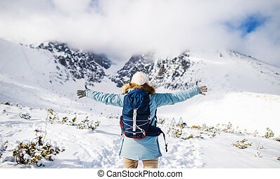 Rear view of young woman standing in snowy winter nature, arms stretched.