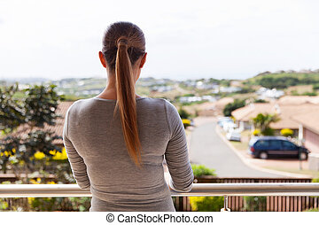 rear view of young woman standing on balcony
