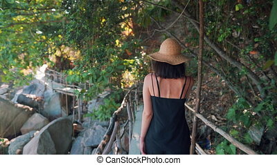 Rear view of young woman walking on wooden bridge in jungle...