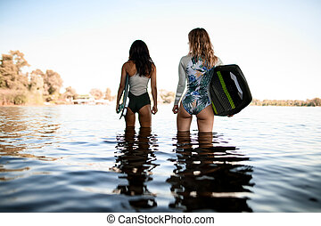 rear view of young women standing in the water and holding surfboards in their hands