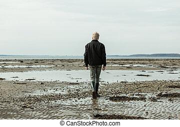 Rear view on single blond boy walking on beach