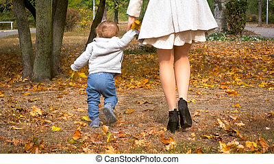 Rear view photo of 1 year old baby boy walking in park with mother