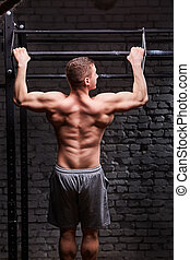Rear view photo of the young muscular male doing exercises...