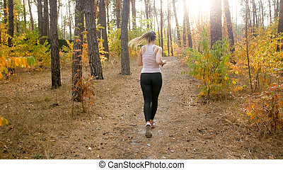 Rear view photo of young sporty woman running in park towards the sun